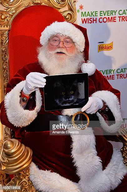 Santa Claus and an iPad photo of Hamilton The Hipster Cat attend the Celebrity Internet Cat Super Group holiday event at Capitol Records Tower on...