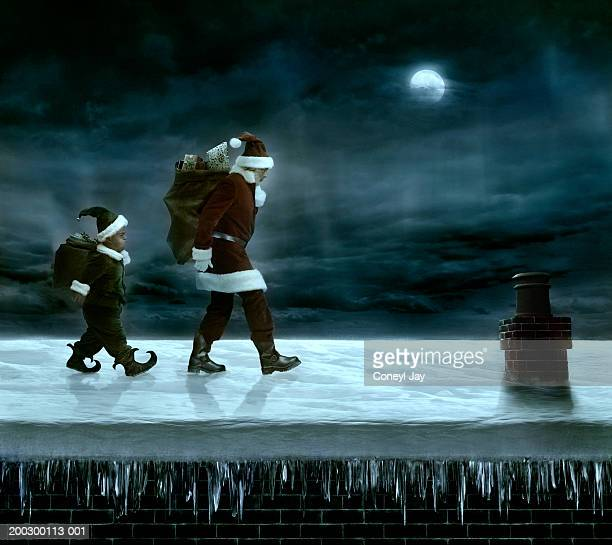 Santa Claus and elf carrying sacks of presents across rooftop