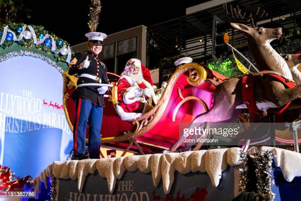 Santa Claus and His Reindeer accompanied by two United States Marine Corps escorts arrive at the 88th Annual Hollywood Christmas Parade on December...