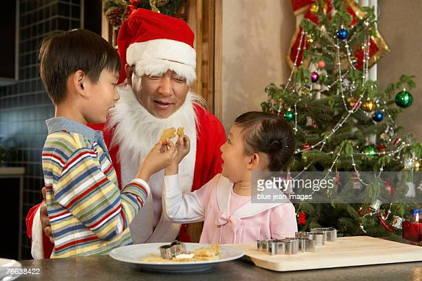 Santa Claus and two kids making Christmas cookies.