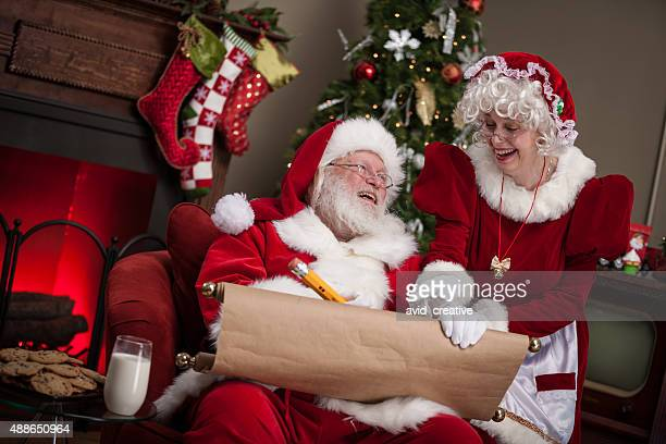santa claus and wife working on naughty and nice list - naughty santa stock photos and pictures