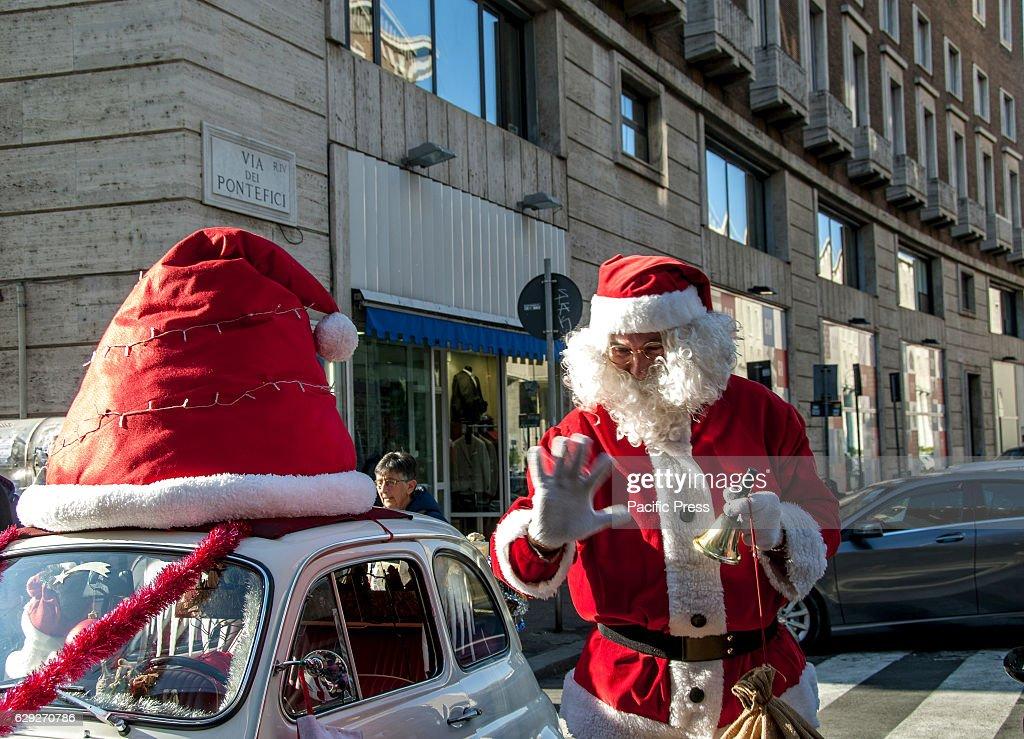 Santa Claus arrives on board of an old car Fiat 500 white... : Nachrichtenfoto