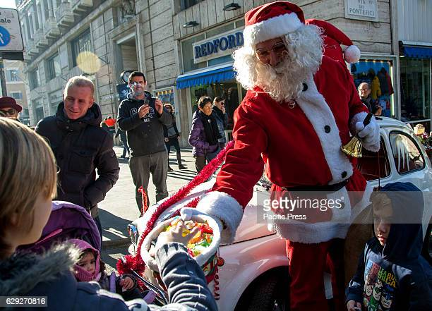 Santa Claus arrives on board of an old car Fiat 500 white with his sack of gifts and candies for children in Rome Via del Corso in the city center