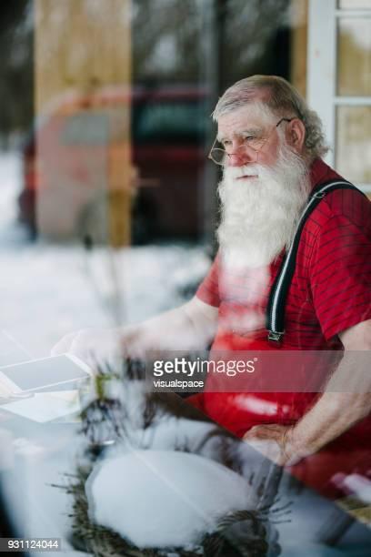 père noël à son salon à l'aide de tablette numérique - pere noel voiture photos et images de collection