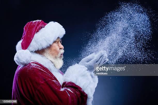 Santa Claus Blasen eine Handvoll Schnee