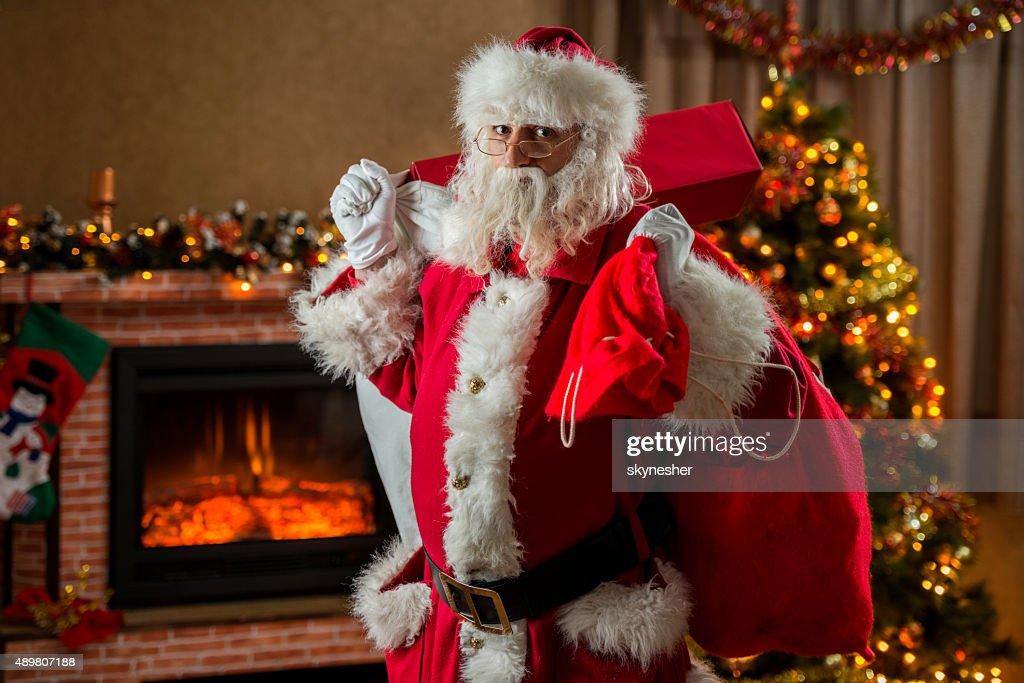 santa claus bringing presents and looking at camera stock photo - Santa Claus Presents