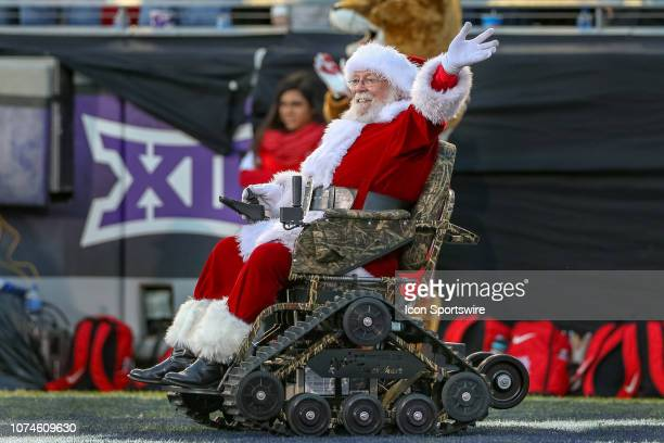 Santa Claus brings out a special allterrain wheel chair to present to a wounded warrior during the Armed Forces Bowl between the Houston Cougars and...