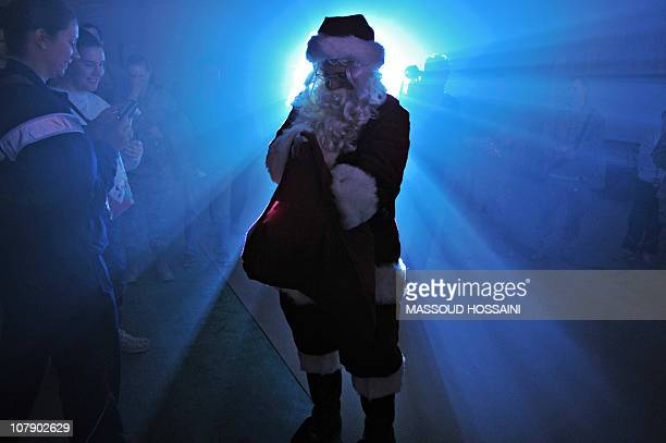 Santa Claus brings presents for US soldiers during a Christmas concert at Bagram Air Base some 50 kms north of Kabul on December 25 2010 Afghan...