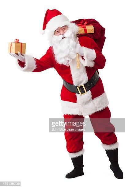 Santa Claus carrying sack of gifts and waving