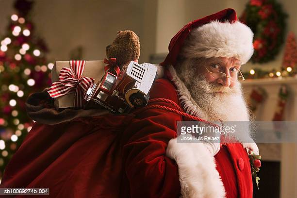 santa claus carrying sack of gifts, portrait, close-up - サンタクロース ストックフォトと画像