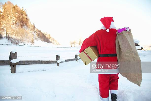 Santa Claus carrying sack of presents walking through snow, rear view