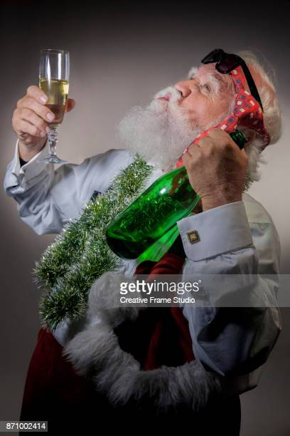 Santa Claus celebrating and howling with a glass of champagne in on hand an a bottle on the other one.
