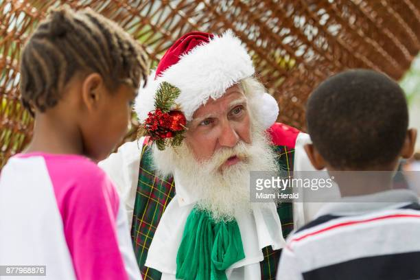 Santa Claus center talks to Kazaria Kamaal left and Keon Kamaal right during the 10th annual Feed a Friend event hosted by Gloria and Emilio Estefan...