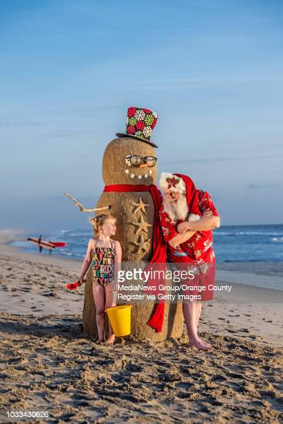 Santa Claus chats with Eden Wenger next to a sand snowman near the Huntington Beach pier in the city of Huntington Beach on Monday December 5 2016