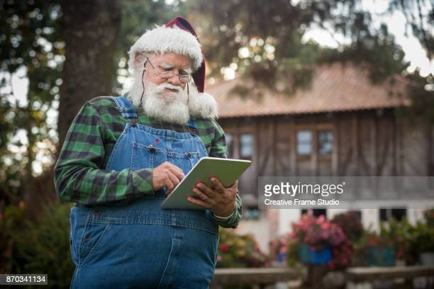 Santa Claus checking his digital tablet in front of his log cabin in the woods