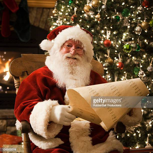 santa claus checking his naughty and nice list - naughty santa stock photos and pictures