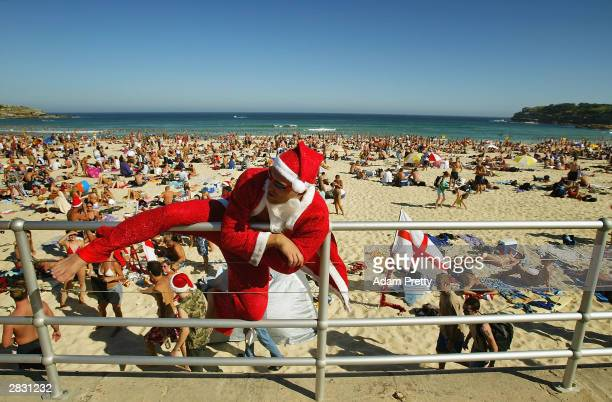 Santa Claus climbs down to the sand as crowds gather on Bondi Beach to celebrate an Australian Christmas in the blazing sun at Bondi Beach December...