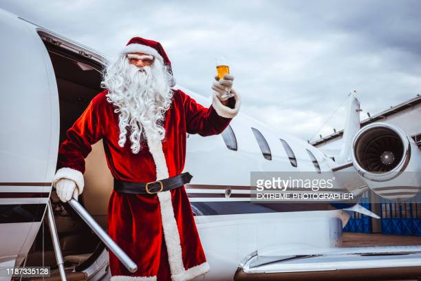 santa claus coming out of a private airplane parked on an airport runway, holding up a glass of champagne - taxiway stock pictures, royalty-free photos & images
