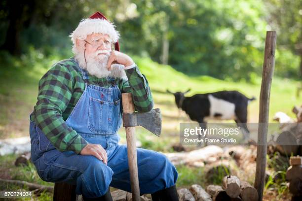 Santa Claus contemplating and resting on a ax after wood cutting on a meadow