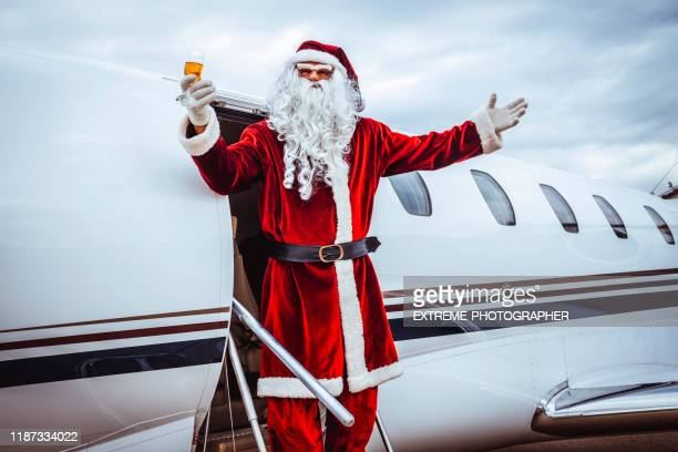 santa claus disembarking a private jet parked on an airport taxiway, holding up a champagne flute with arms raised - taxiway stock pictures, royalty-free photos & images