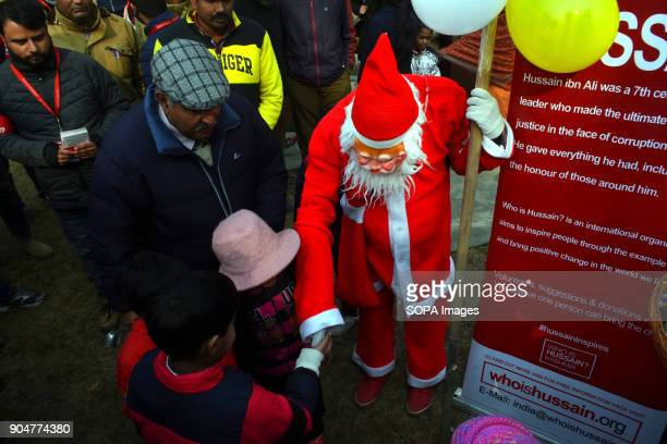 Santa Claus distributes candies among kids outside the Holy Family Catholic Church during Christmas in Srinagar Indian administered Kashmir The...