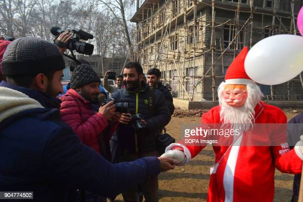 Santa Claus distributes candies among the press photographers outside the Holy Family Catholic Church during Christmas in Srinagar Indian...