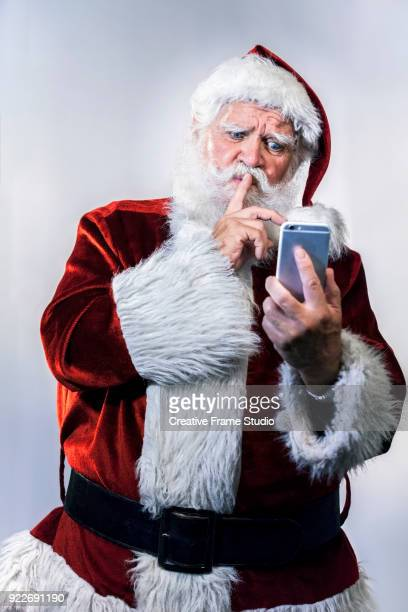 Santa Claus doing silence gesture with his finger looking a smart phone