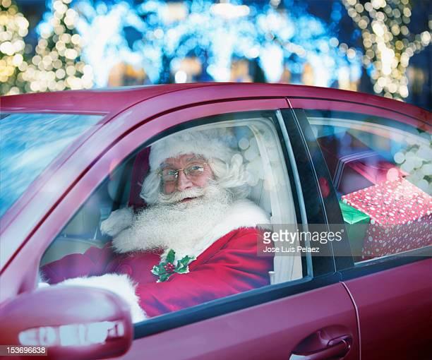 Santa claus driving a car full of presents
