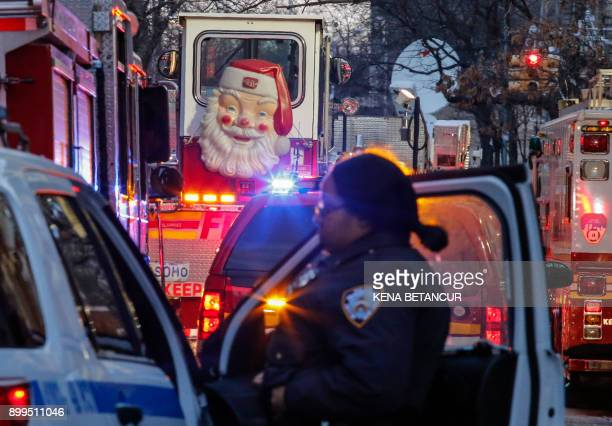 A Santa Claus figure is seen on the door of a fire truck as a New York Police Department officer works on the scene of an apartment fire on December...