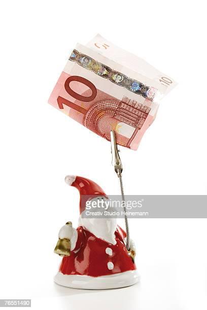 Santa Claus figurine holding Euro note