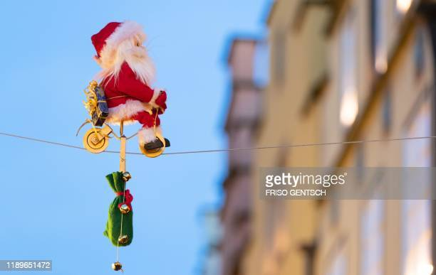 A Santa Claus figurine on a toy bike drives on a tightrope spanning over the Christmas market in Osnabrueck northwestern Germany on December 19 2019...