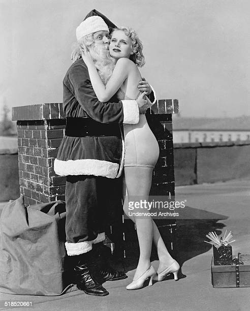 Santa Claus gets a warm rooftop welcome from a pretty blonde woman in a bathing suit California late 1930s