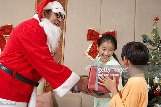 Santa Claus giving Christmas gifts to two children.