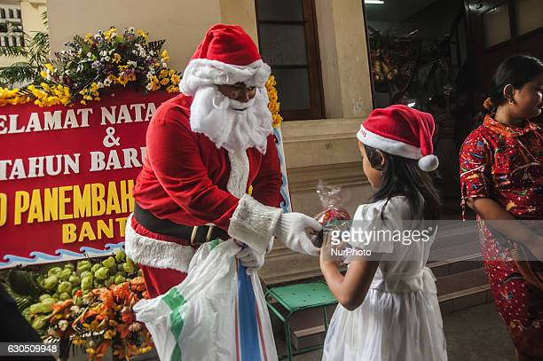 Santa Claus giving gifts to a child when attend mass in celebration of Christmas in Sacred Heart of Jesus Catholic Church in Yogyakarta Indonesia on...