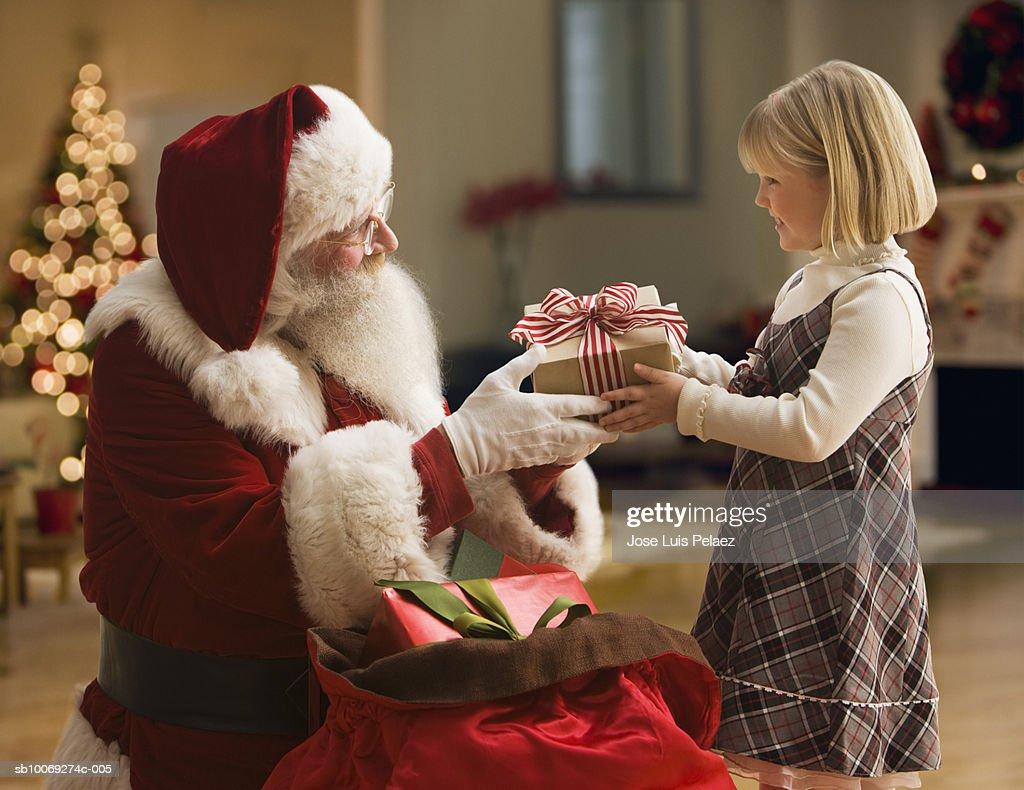 Santa Claus giving girl (4-5) gift, side view : Stockfoto