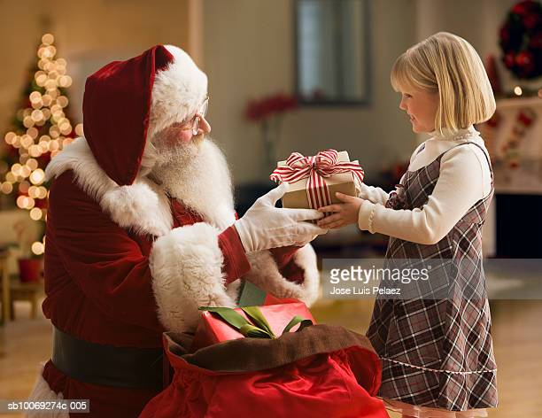 Santa Claus giving girl (4-5) gift, side view