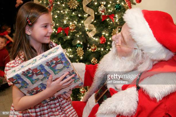 Santa Claus giving presents to coworkers children at an office Christmas party in Miami