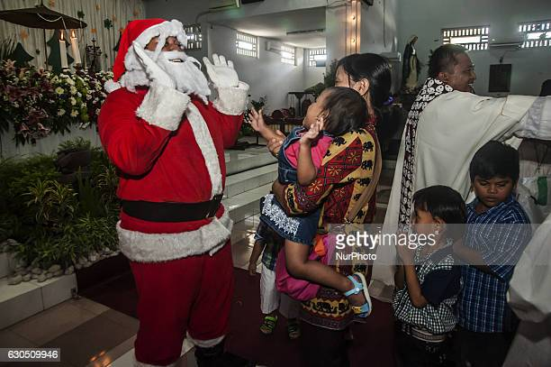Santa Claus greets childrens when attend mass in celebration of Christmas in Sacred Heart of Jesus Catholic Church in Yogyakarta Indonesia on...