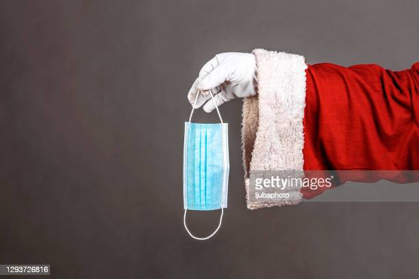 santa claus hands holding a coronavirus surgical face mask. - formal glove stock pictures, royalty-free photos & images