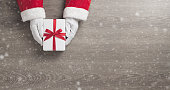Santa claus hands is holding a white gift box with red ribbon