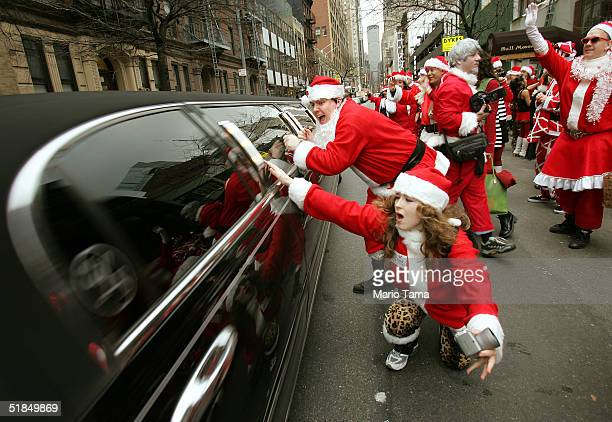 Santa Claus' hassle a limo driving on 44th Street while others participate in the 2004 Santacon December 11 2004 in New York City The annual event...