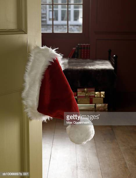 santa claus hat hanging on door knob - santa hat stock photos and pictures