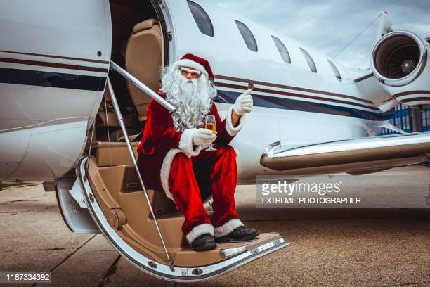 santa claus having a seat on the stairs of a parked private airplane parked on an airport taxiway with a glass of champagne, giving thumbs up. - taxiway stock pictures, royalty-free photos & images
