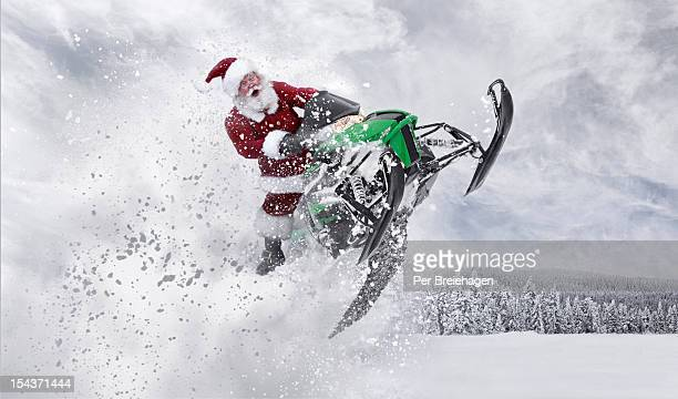 Santa Claus having fun with his snowmobile