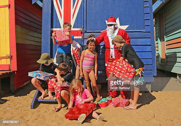 Santa Claus helps children open their Christmas presents on Christmas Day at Brighton Beach on December 25 2013 in Melbourne Australia Brighton Beach...