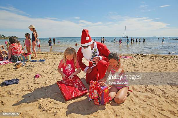 Santa Claus helps children to open their Christmas presents on Christmas Day at Brighton Beach on December 25 2013 in Melbourne Australia Brighton...