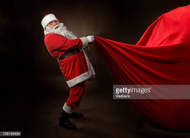 santa claus holding a big gift bag - provincial reconstruction team stock photos and pictures