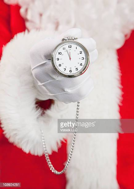 Santa Claus holding a pocket watch in his hand