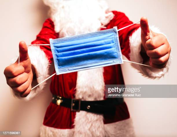 santa claus holding a protective face mask - 2020 stock pictures, royalty-free photos & images
