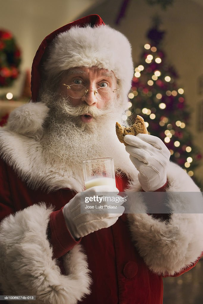 Santa Claus holding biscuit and glass of milk, portrait, close-up : Stockfoto